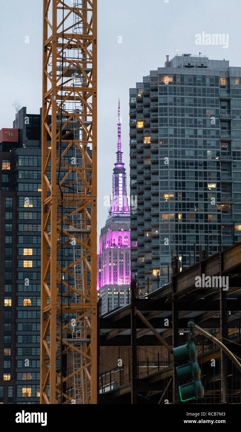 New York City, United States - November 17 2018:   The Empire state building lit in Purple seen between other skyscrapers As seen from 12th Avenue Stock Photo