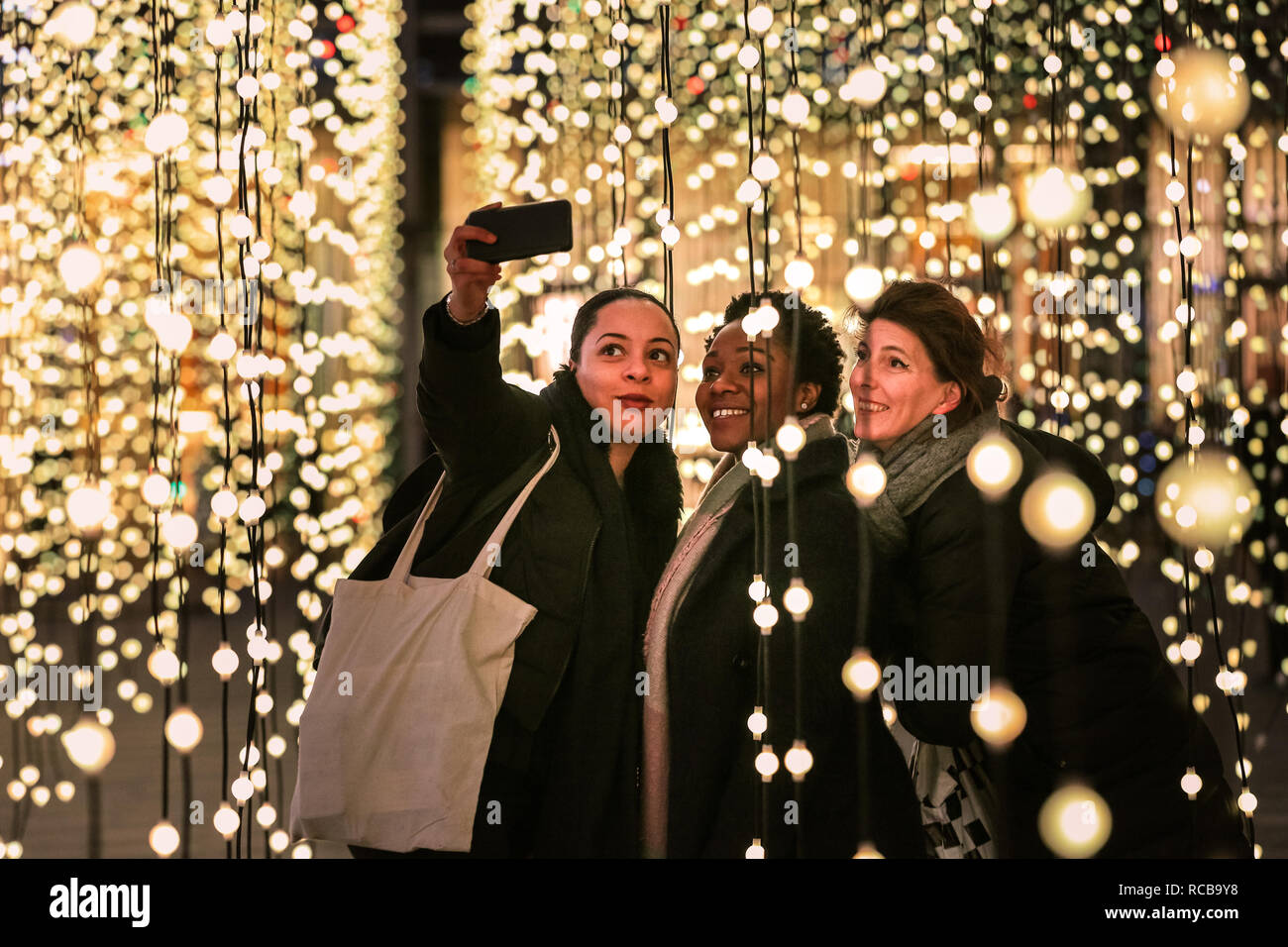 Canary Wharf, London, UK, 14th Jan 2019. People interact with and take selfies with the 'Submergence' installation, a large work incorporating strings of hanging lights by arts collective Squidsoup. The colourful Canary Wharf Winter Lights installations once again open to public viewing and interactive fun in and around Canary Wharf from Jan 15th until Jan 26th. Credit: Imageplotter News and Sports/Alamy Live News - Stock Image