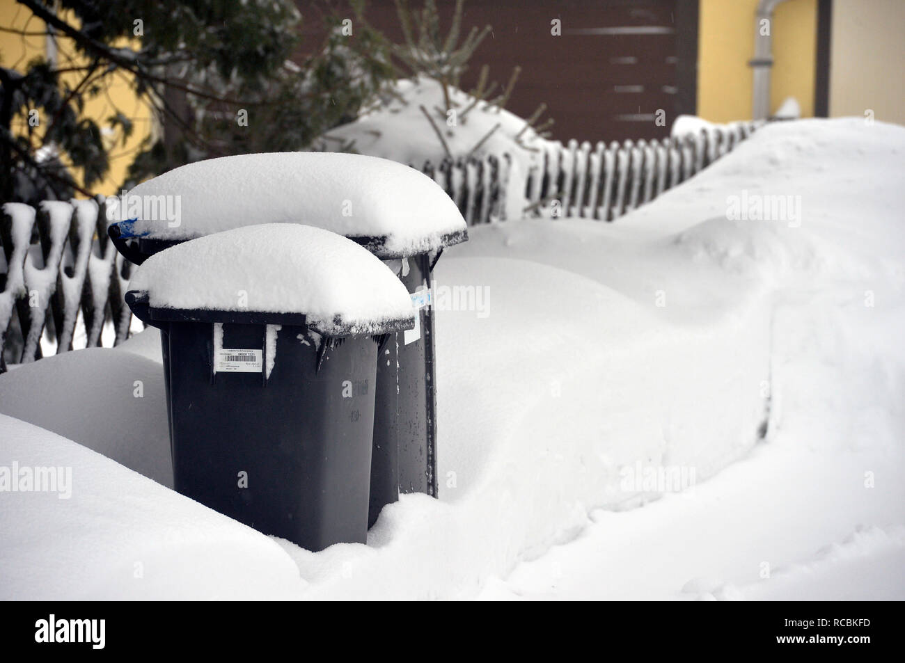 10 January 2019, Saxony, Schönheide: Garbage bins and yellow sacks are snowed in on a property in Schönheide, Saxony. In winter, garbage trucks often have a hard time emptying the containers. Photo: Volkmar Heinz/dpa-Zentralbild/ZB - Stock Image