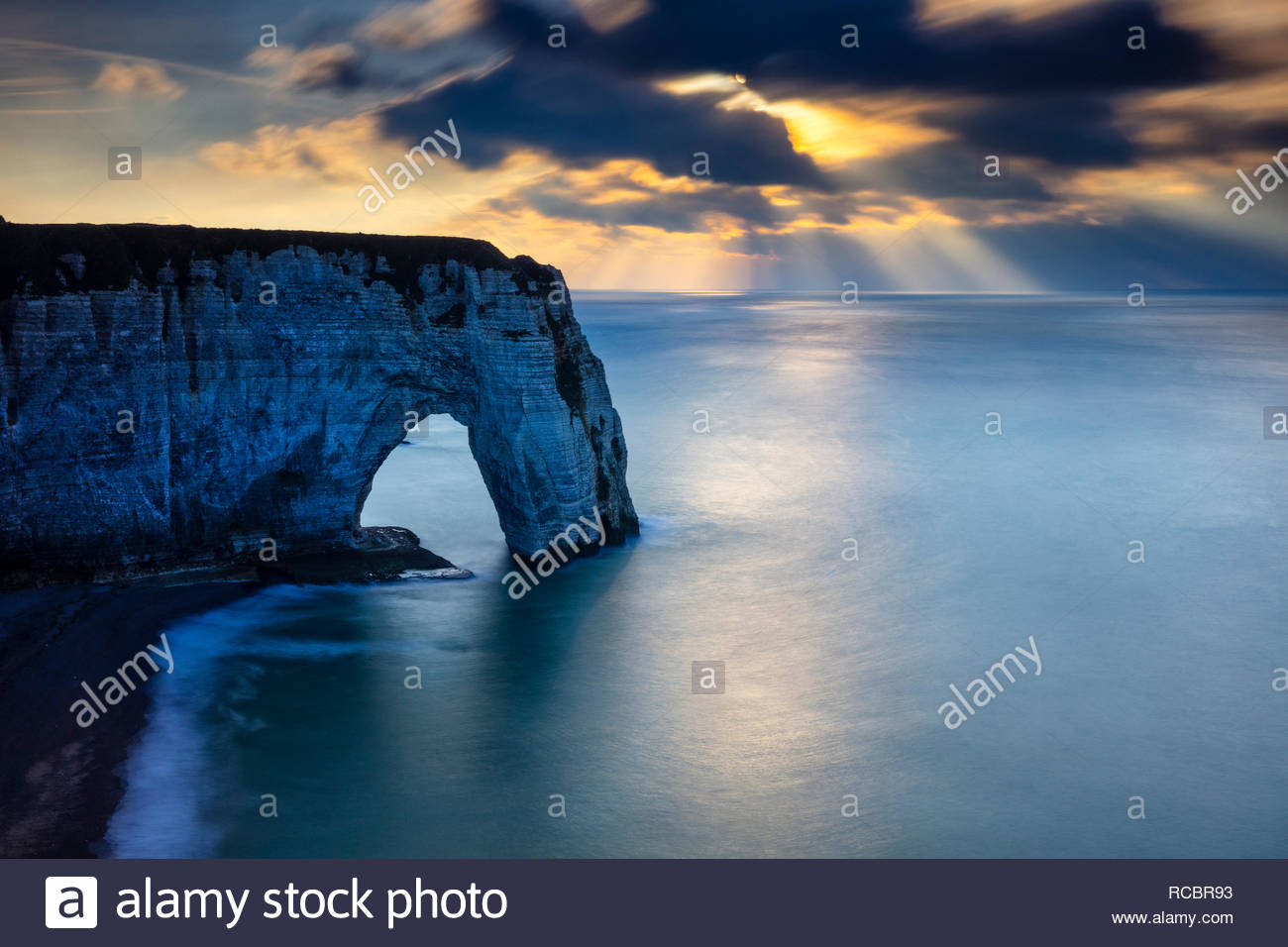 Crepuscular Rays, also known as god beams, form over the Atlantic Ocean and a large sea arch called Manneporte in the late afternoon in Étretat, Franc - Stock Image