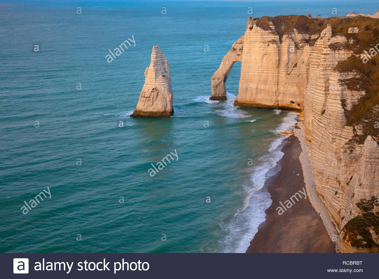 The sea arch Porte d'Aval and the sea stack L'Aiguille (the Needle) stand in the Atlantic Ocean next to the cliffs of Étretat in Normandy, France. - Stock Image