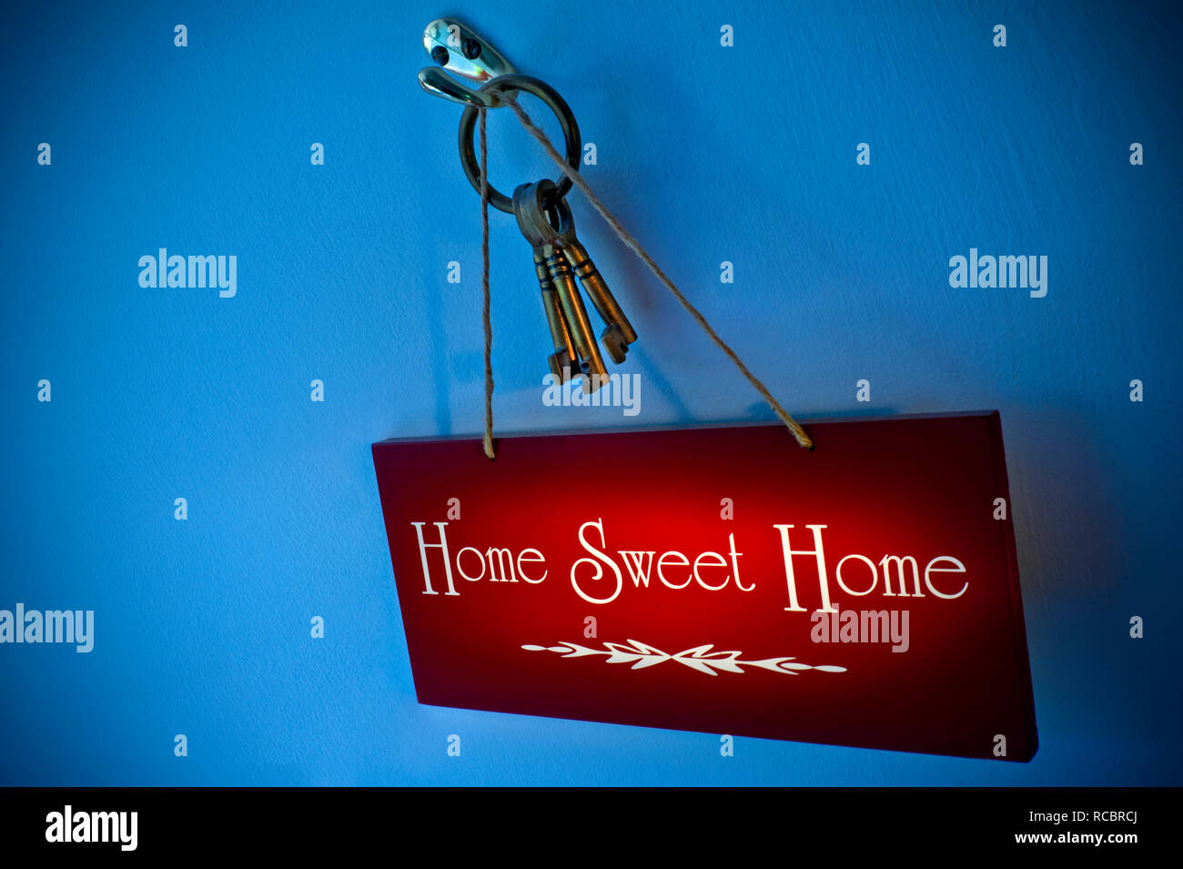 Atmospheric Concept Home Owner 'Home Sweet Home' sign hanging with house keys on hook with small shaft of warm light illuminating the sign with cool light surrounding - Stock Image