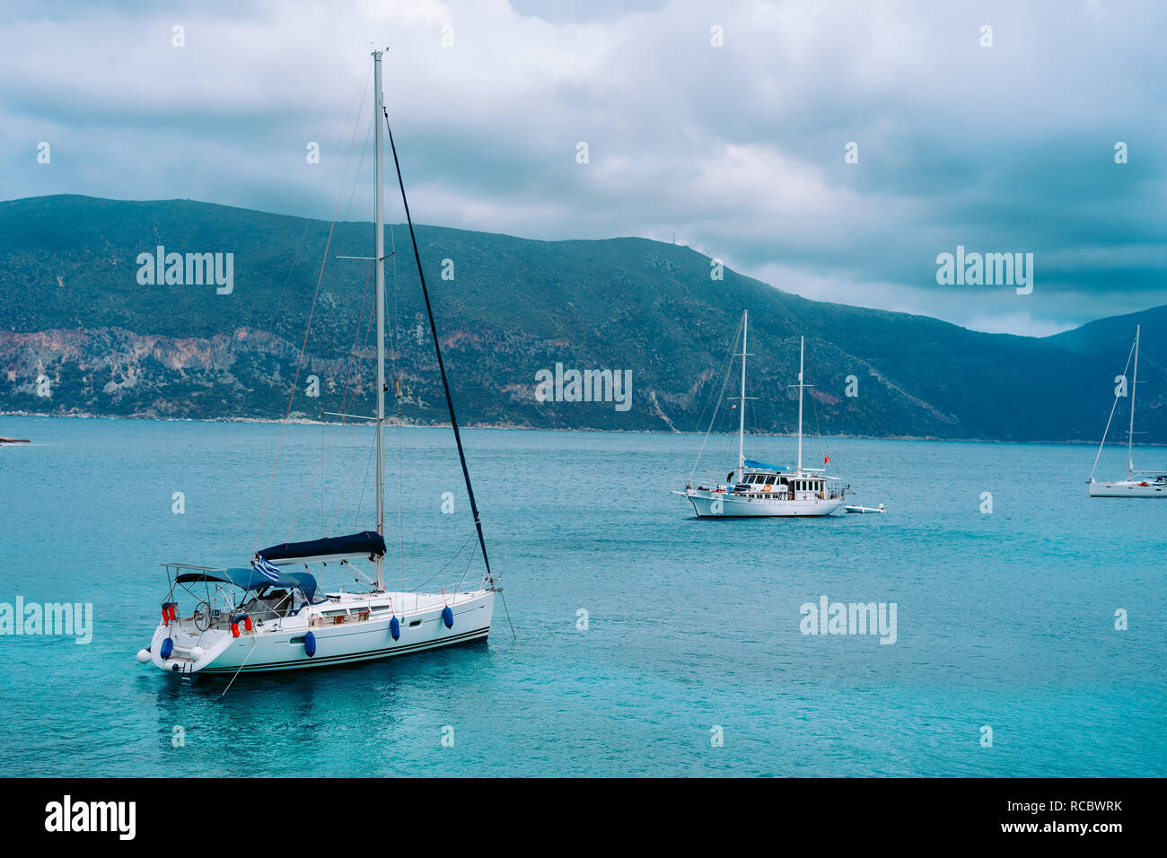 Yachts anchored near beautiful greek shoreline, on an overcast day in summer, coastal, travel, vacation concept - Stock Image