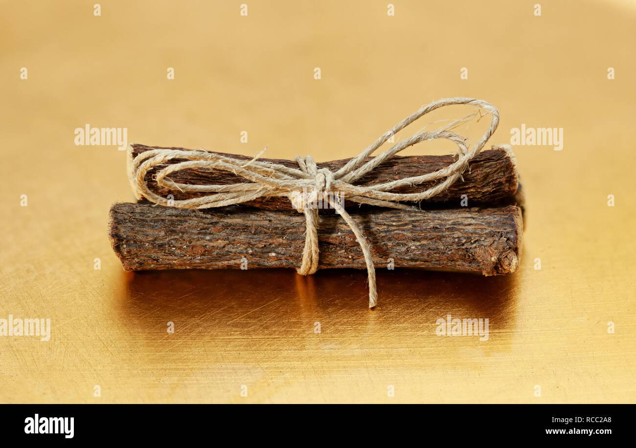 Bundle of licorice roots Glycyrrhiza glabra on golden table. - Stock Image