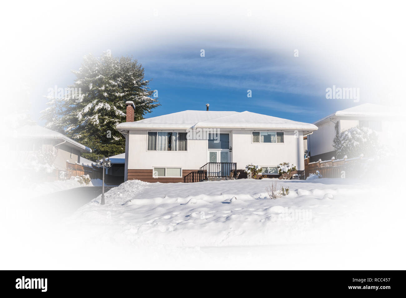 Old modest residential house in snow on sunny winter day - Stock Image