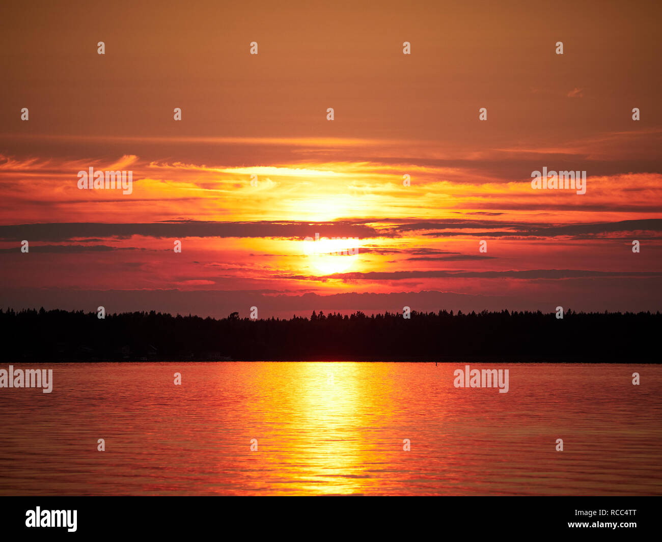 Red sunset sky with the sun and colorful clouds above a peaceful sea in  Vaasa, Finland. The bright disk of the sun is partly hidden by the clouds. - Stock Image