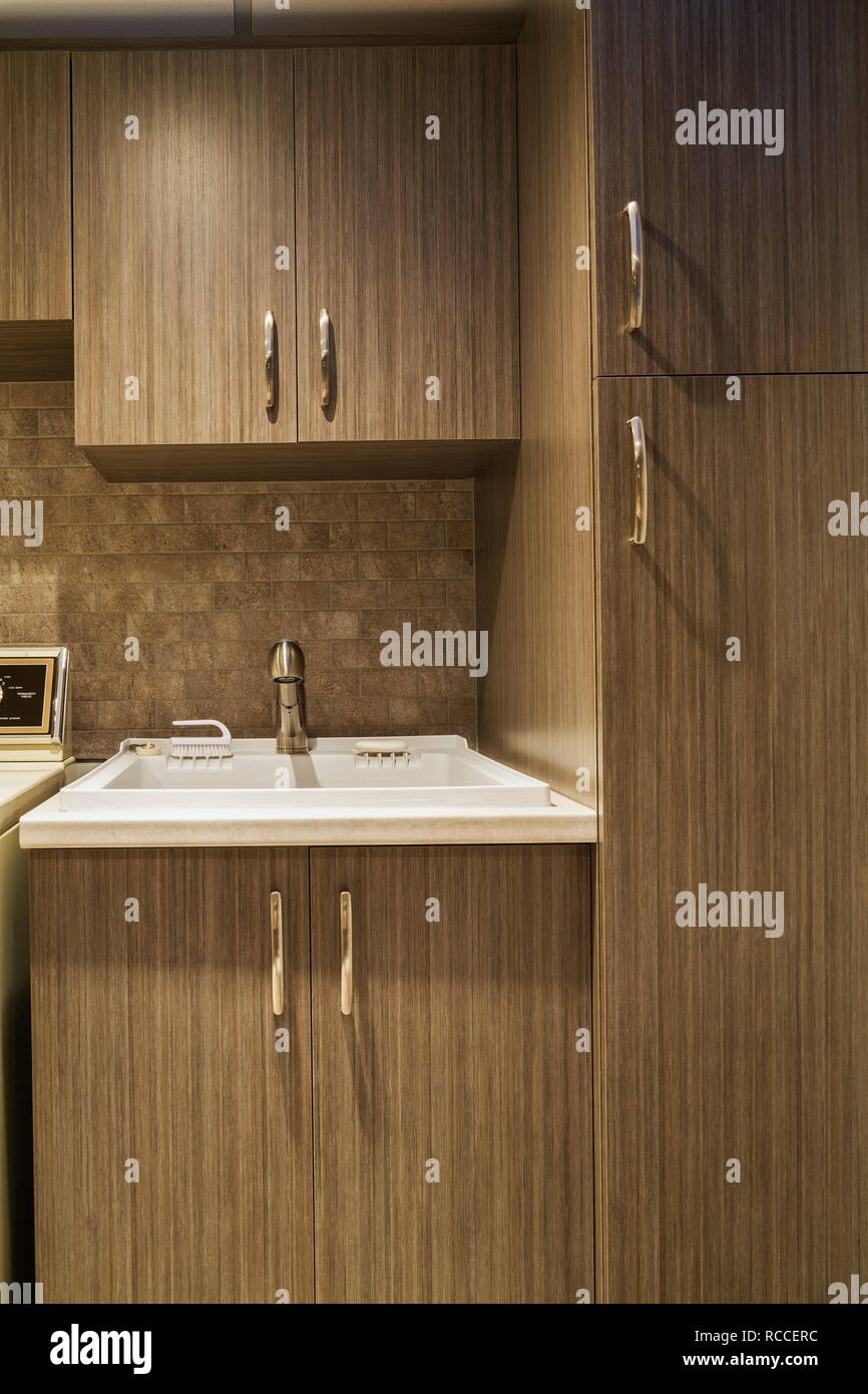 Newly Installed Brown Wood Veneer Cabinets And White Utility