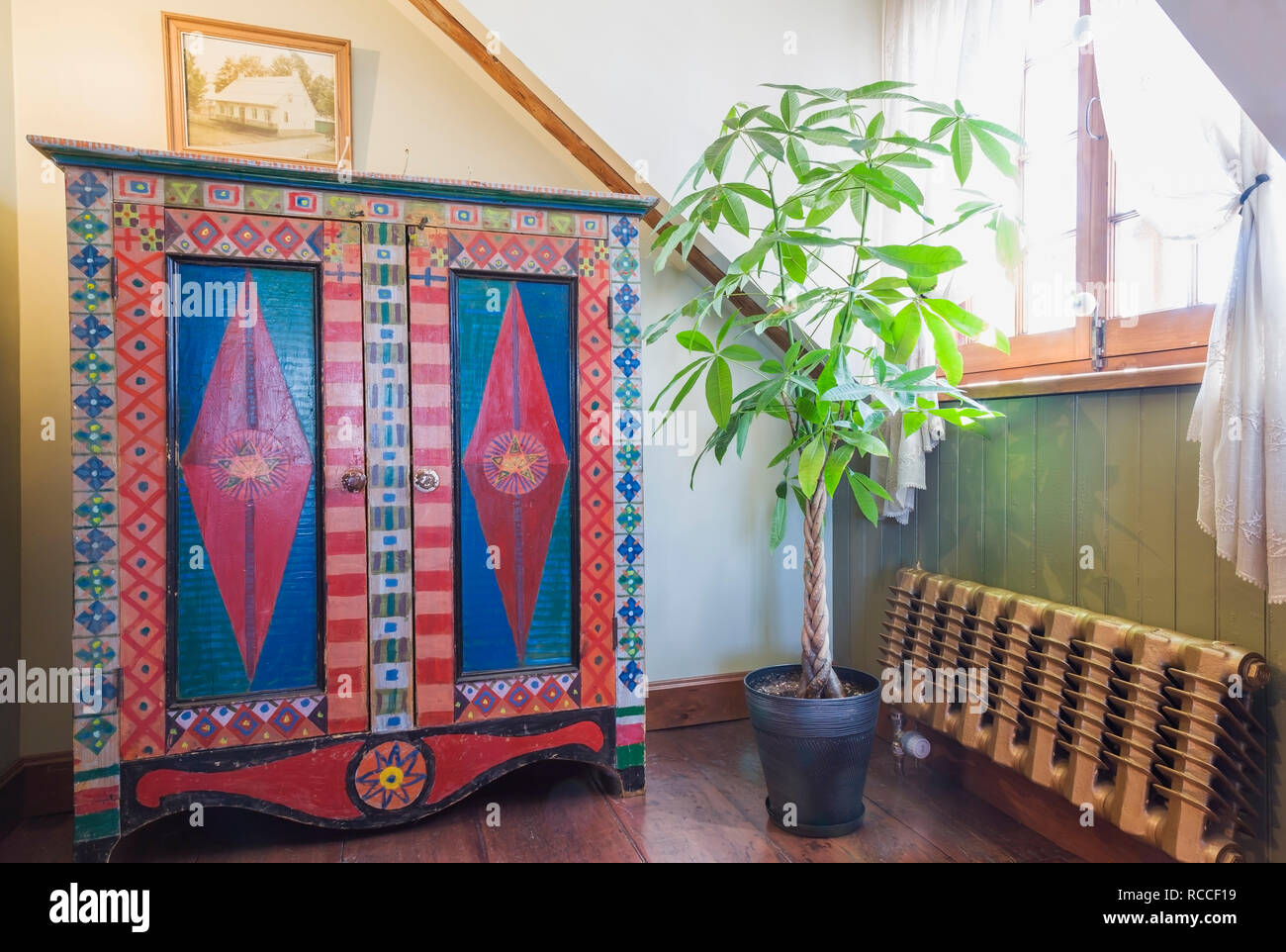 Master bedroom with colourful wooden antique armoire with diamond point design, green house plant next to old hot water heating radiator in old house - Stock Image