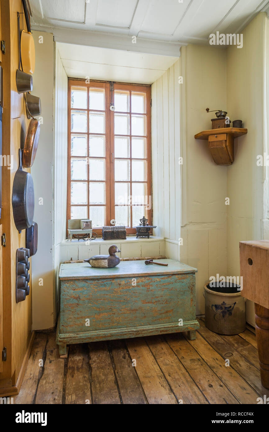 Kitchen corner wall with tin and copper cooking pots, pans and faded turquoise painted antique wooden storage chest inside an old 1835 fieldstone home - Stock Image