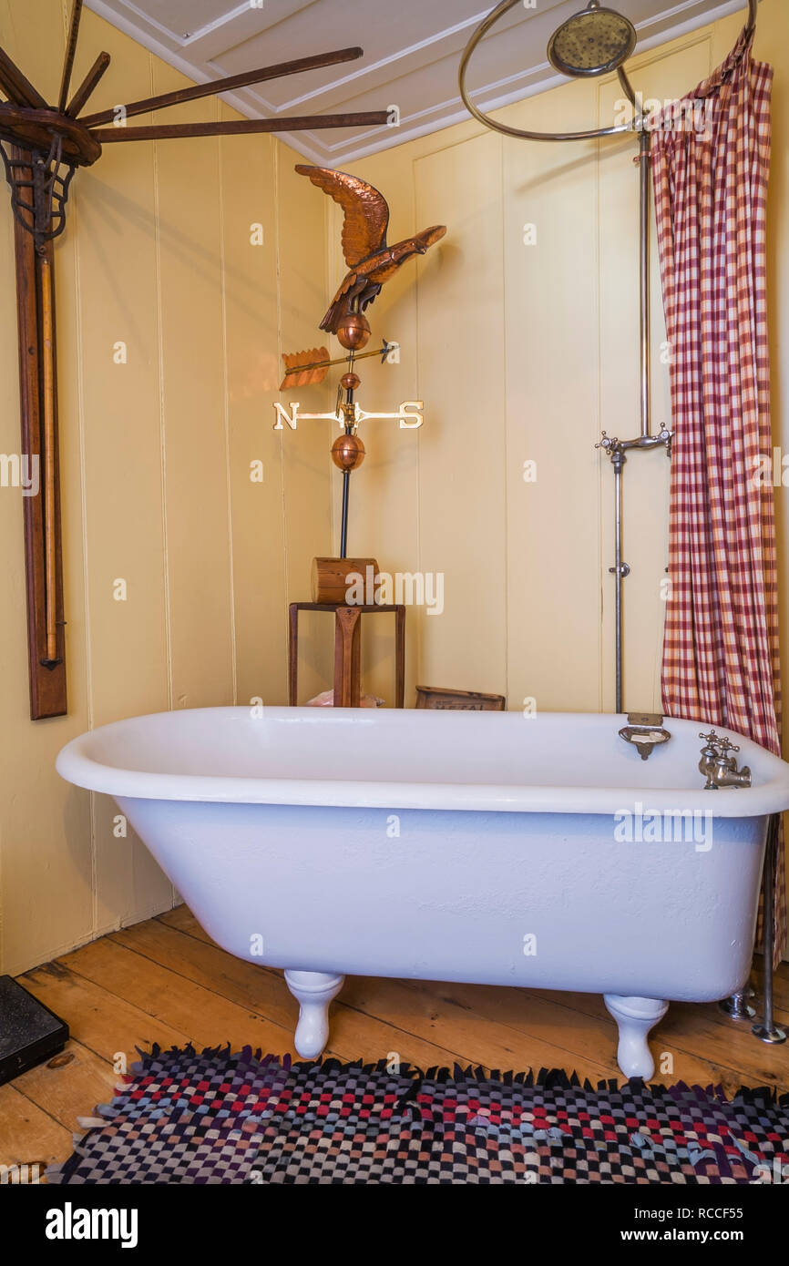 Freestanding clawfoot bathtub in main bathroom with yellow walls on ground floor inside an old 1835 fieldstone house - Stock Image