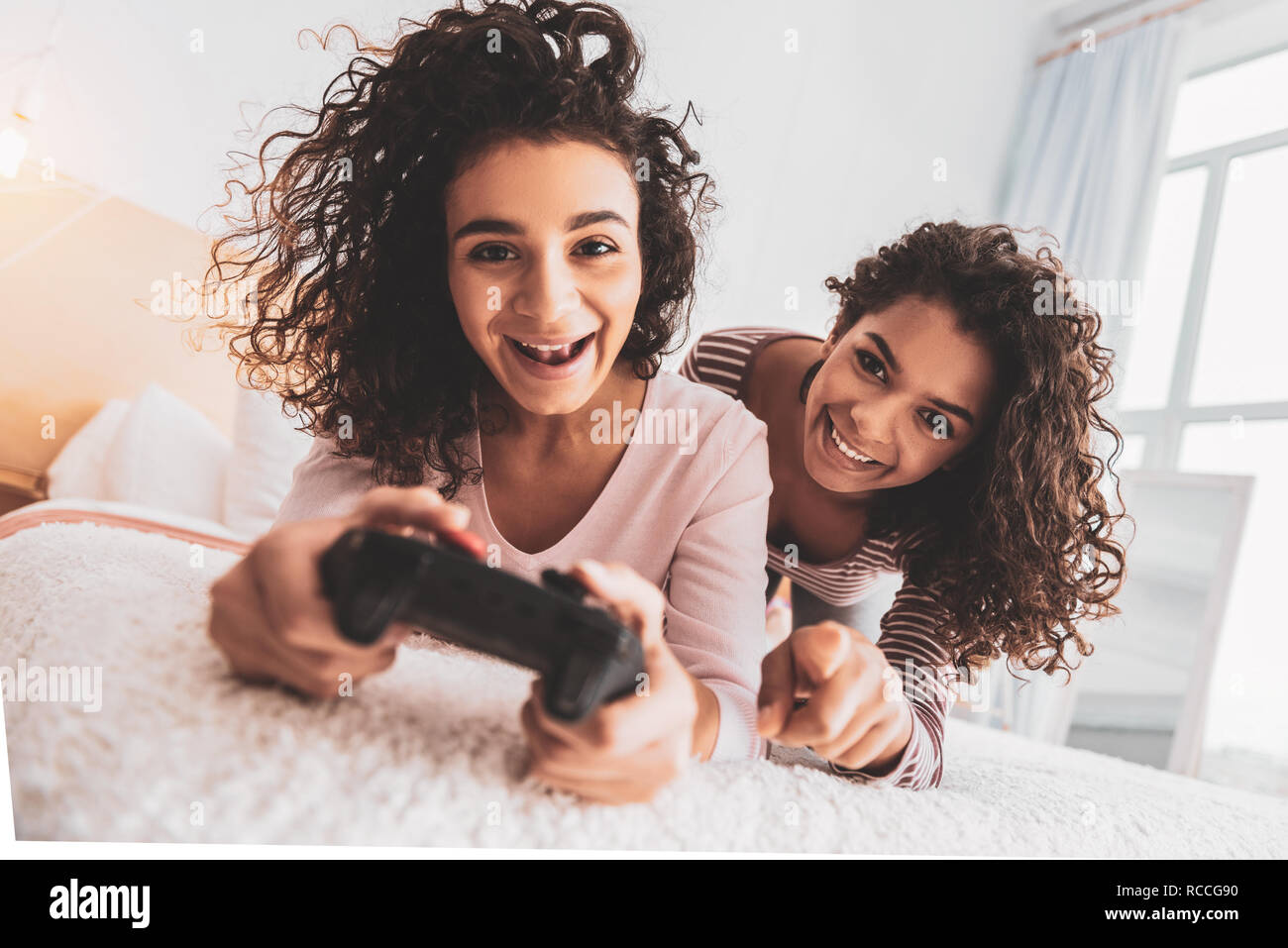 Friends laughing while spending free time with play station - Stock Image