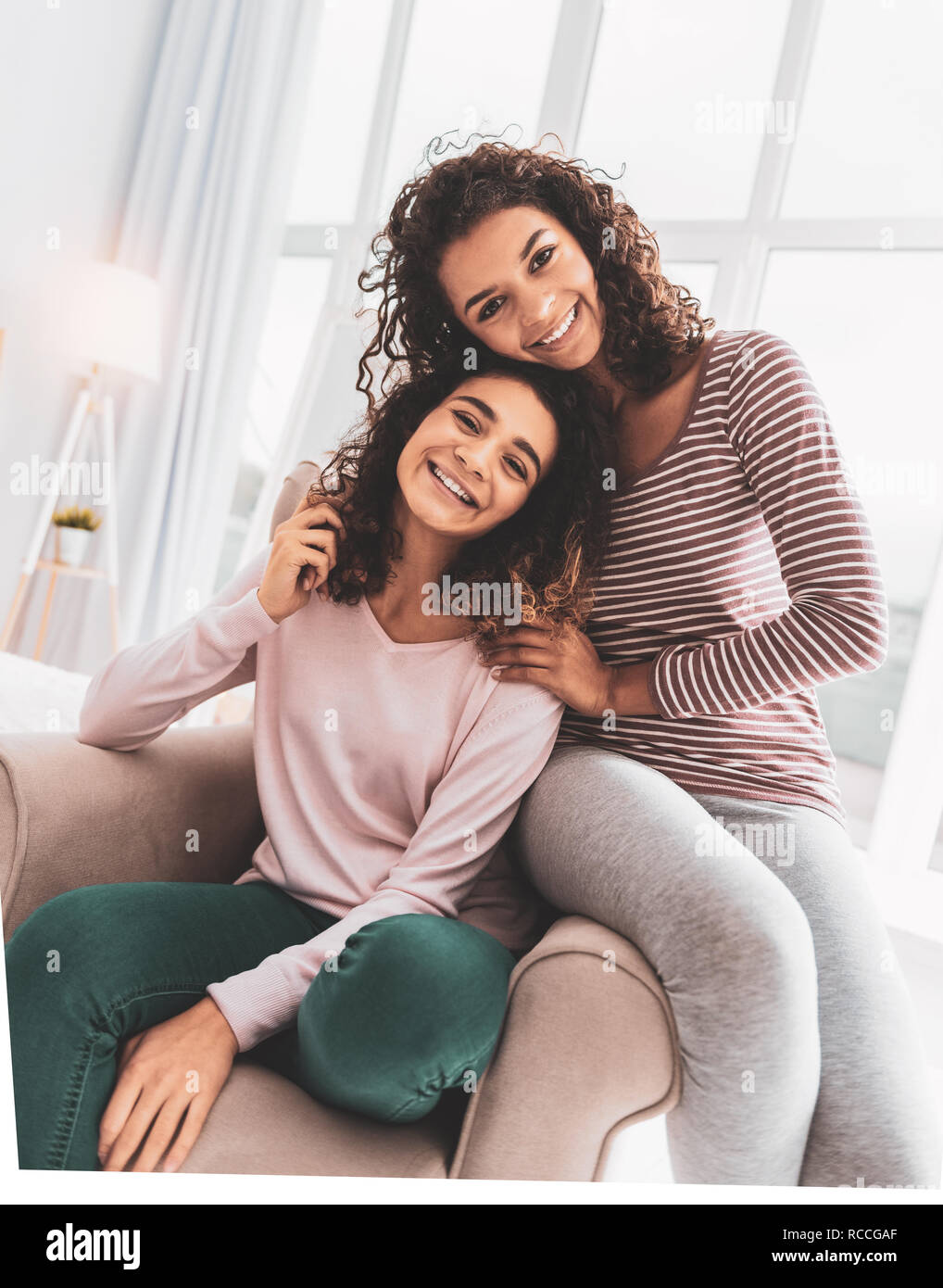 Smiling sister in grey leggings sitting near her older sister - Stock Image
