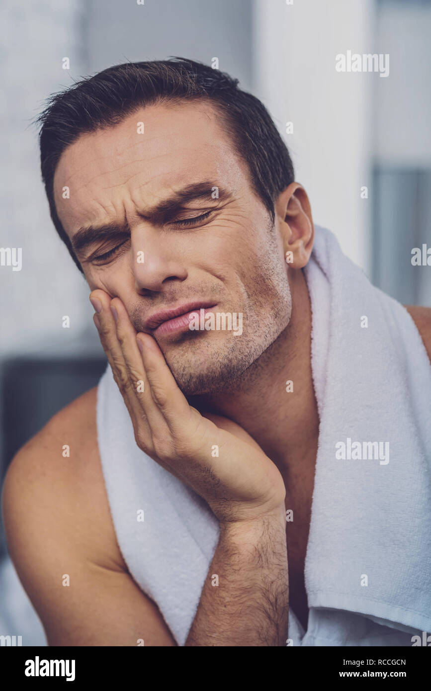 Sad unhappy man suffering from toothache - Stock Image