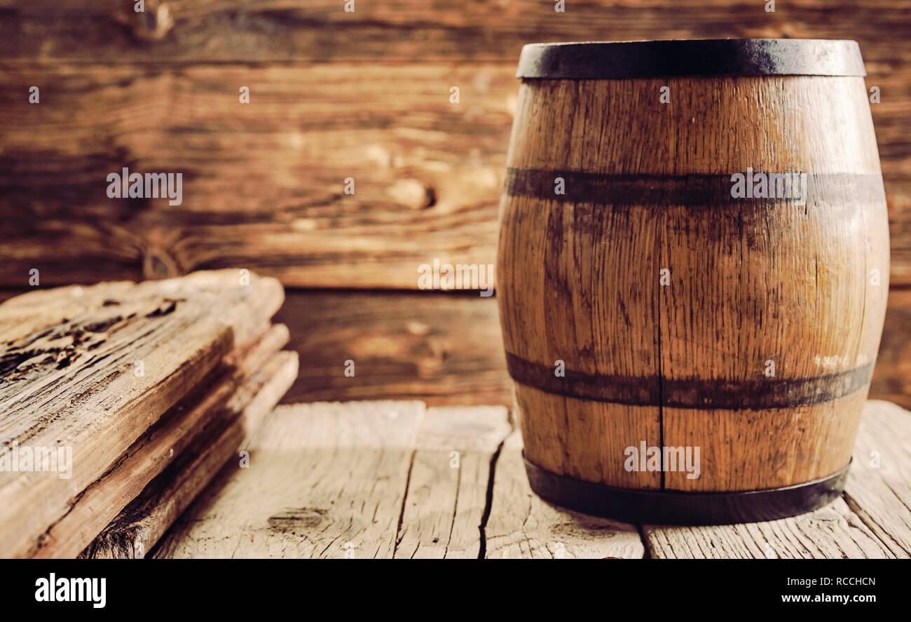Oak barrel for alcohol aging, standing on old wooden table in rustic house. Copy space - Stock Image