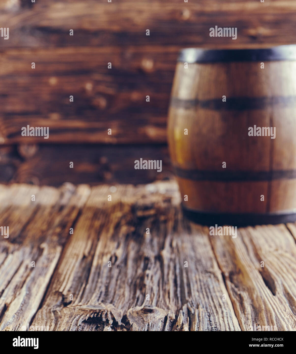 Oak barrel for alcohol aging, standing on old wooden table with harsh woodgrain, blurred in background - Stock Image