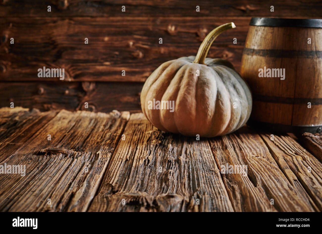 Big pumpkin and oak barrel in wooden house room on table with old harsh woodgrain surface. Rustic harvest concept in brown with copy space - Stock Image