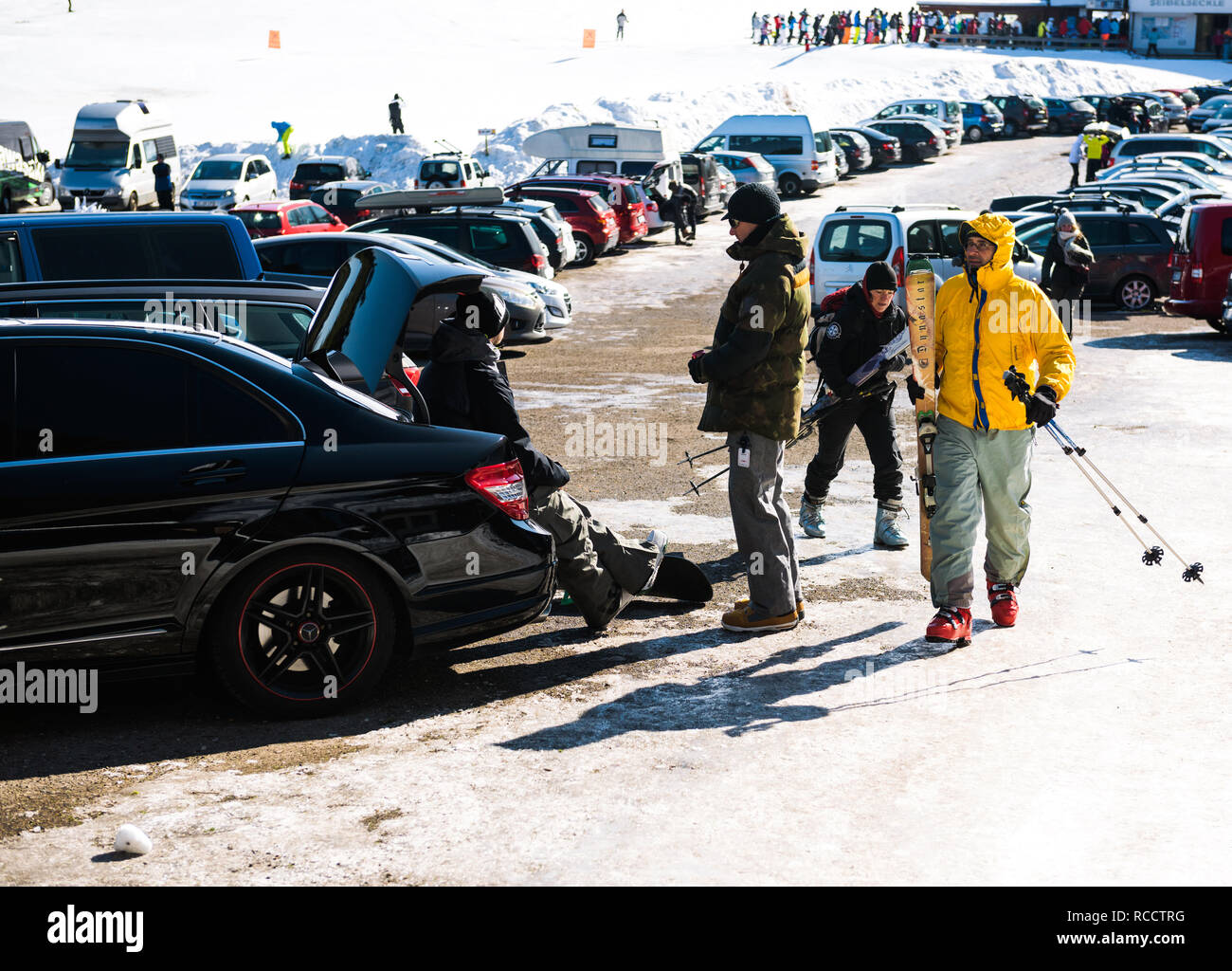 SEEBACH MUMMELSEE, FEB 25, 2018: Snowboarders resting after game seated on a Mercedes-Benz fast car parked in large parking Stock Photo