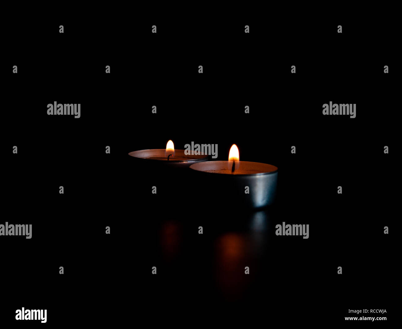 Two lighted candles with an orange flame and isolated on a black background - Stock Image
