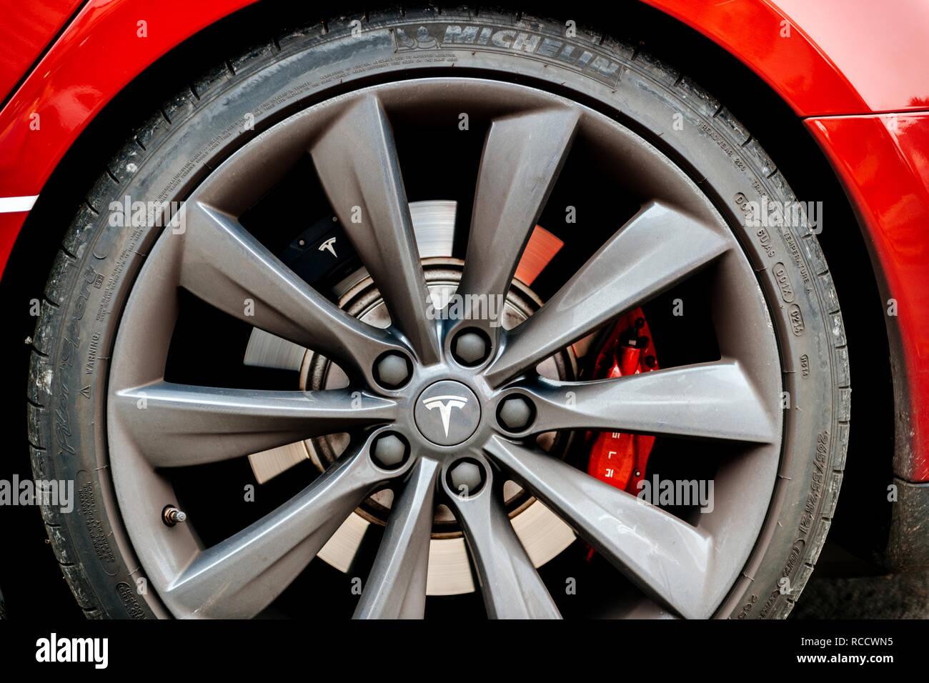PARIS, FRANCE - NOV 29, 2014: Close-up of aluminium rim of luxury electric red Tesla Model S car wheel with distinct logotype insignia parked on street - Stock Image