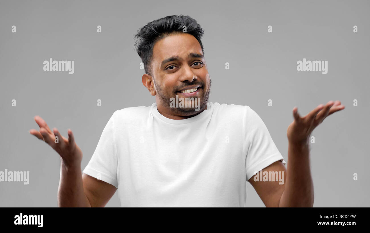 confused indian man shrugging - Stock Image