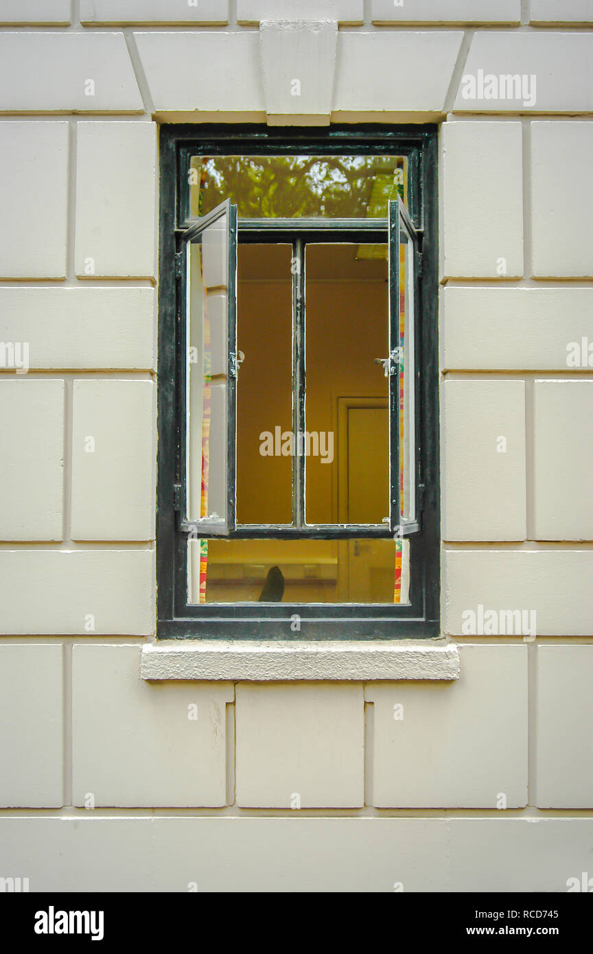 two opened metal framed windows in a house with white facia - Stock Image
