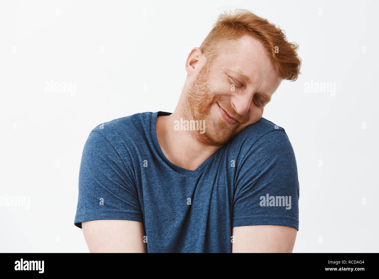 Silly and funny caucasian redhead guy with bristle, tilting head and leaning on shoulder with lovely and cute expression, smiling with closed eyes being tender and girly over gray background - Stock Image