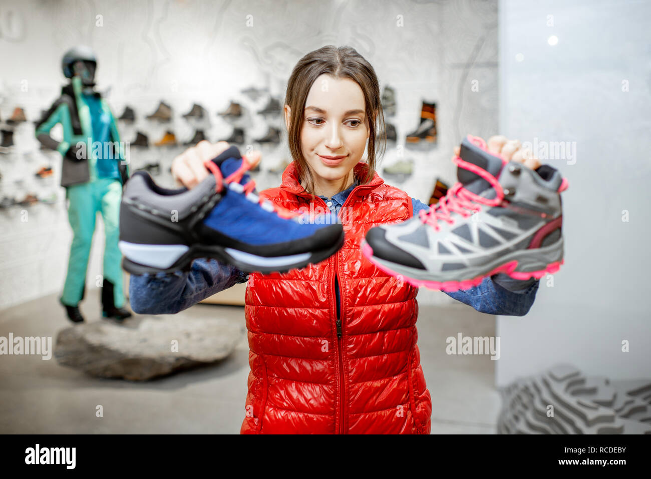 Young woman choosing trail shoes for mountain hiking in the modern sports shop Stock Photo