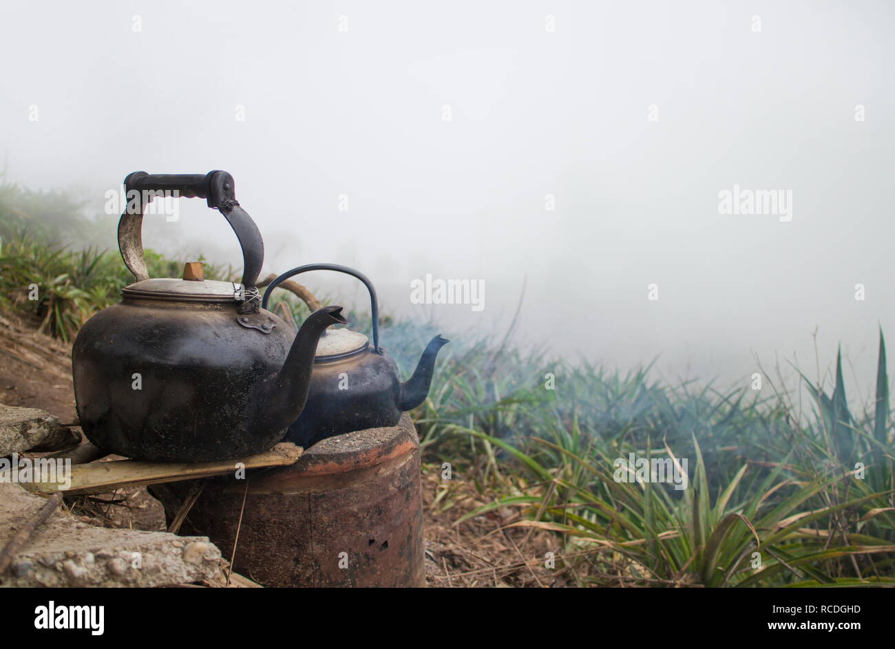 Kettle water on the old stove at field on mountain with fog in winter. - Stock Image