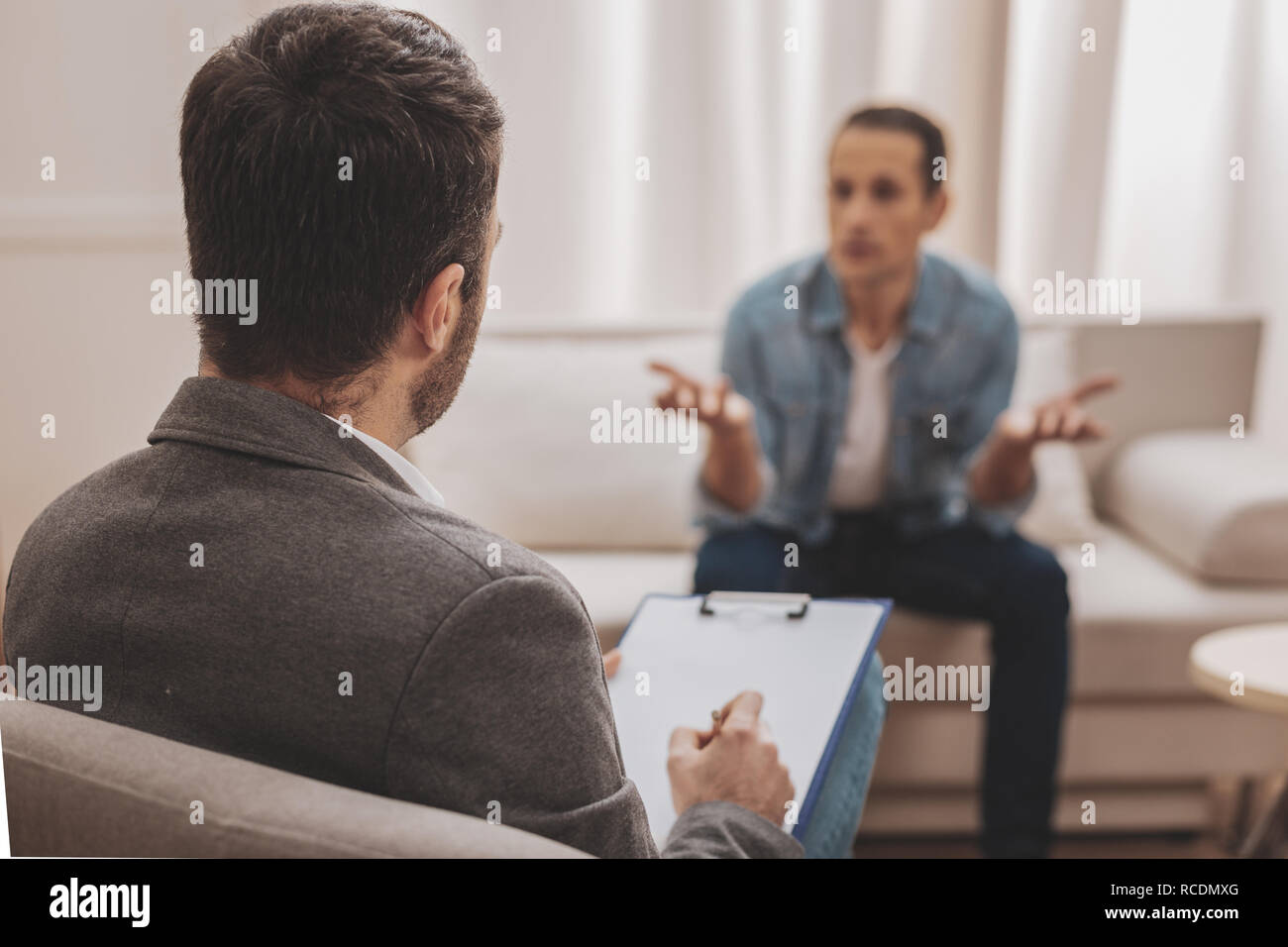 Psychologist wearing grey jacket listening to his anxious client - Stock Image