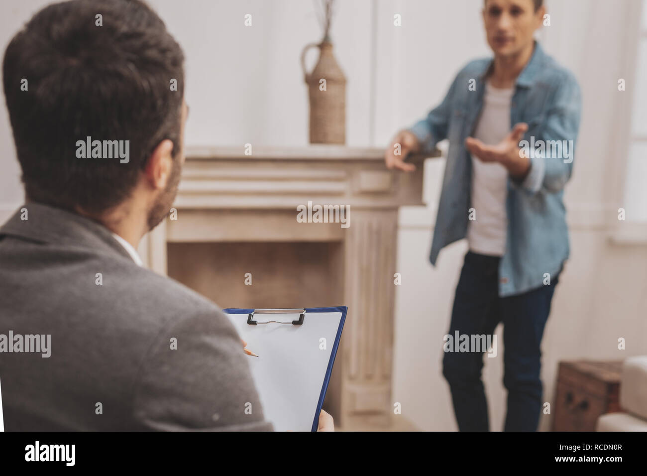 Observant psychologist making notes during therapy session - Stock Image