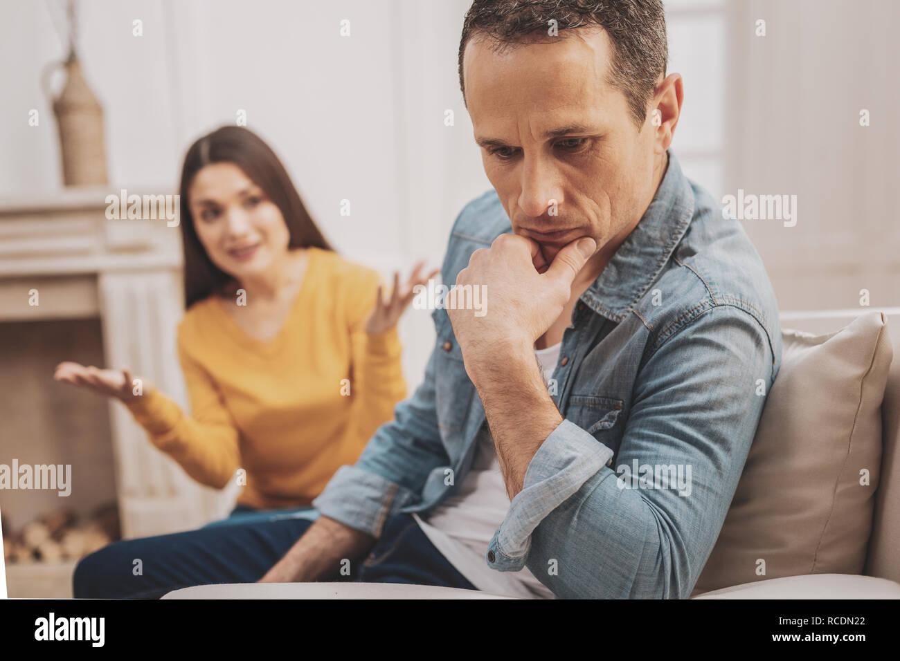 Mature man wearing denim shirt feeling thoughtful - Stock Image