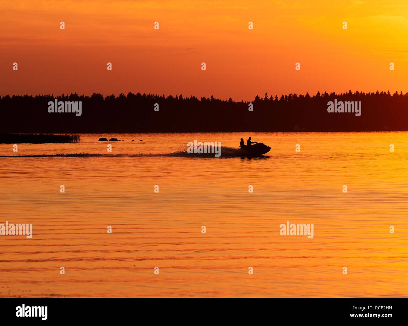 A jet-ski driving in calm sea water in Vaasa, Finland.  Sunset sky and colorful waves in the water.  activity, hobby and leisure time consept. - Stock Image