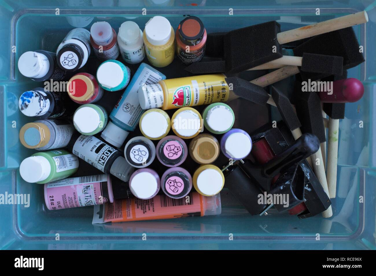 A plastic container full of acrylic paints, foam brushes, and rollers, as seen from above. - Stock Image