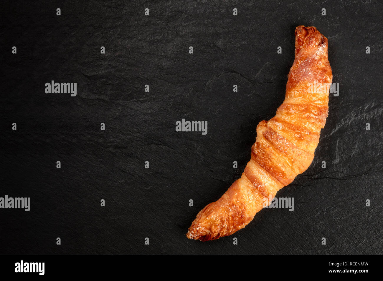 A croissant on a black background, shot from above, with copy space - Stock Image