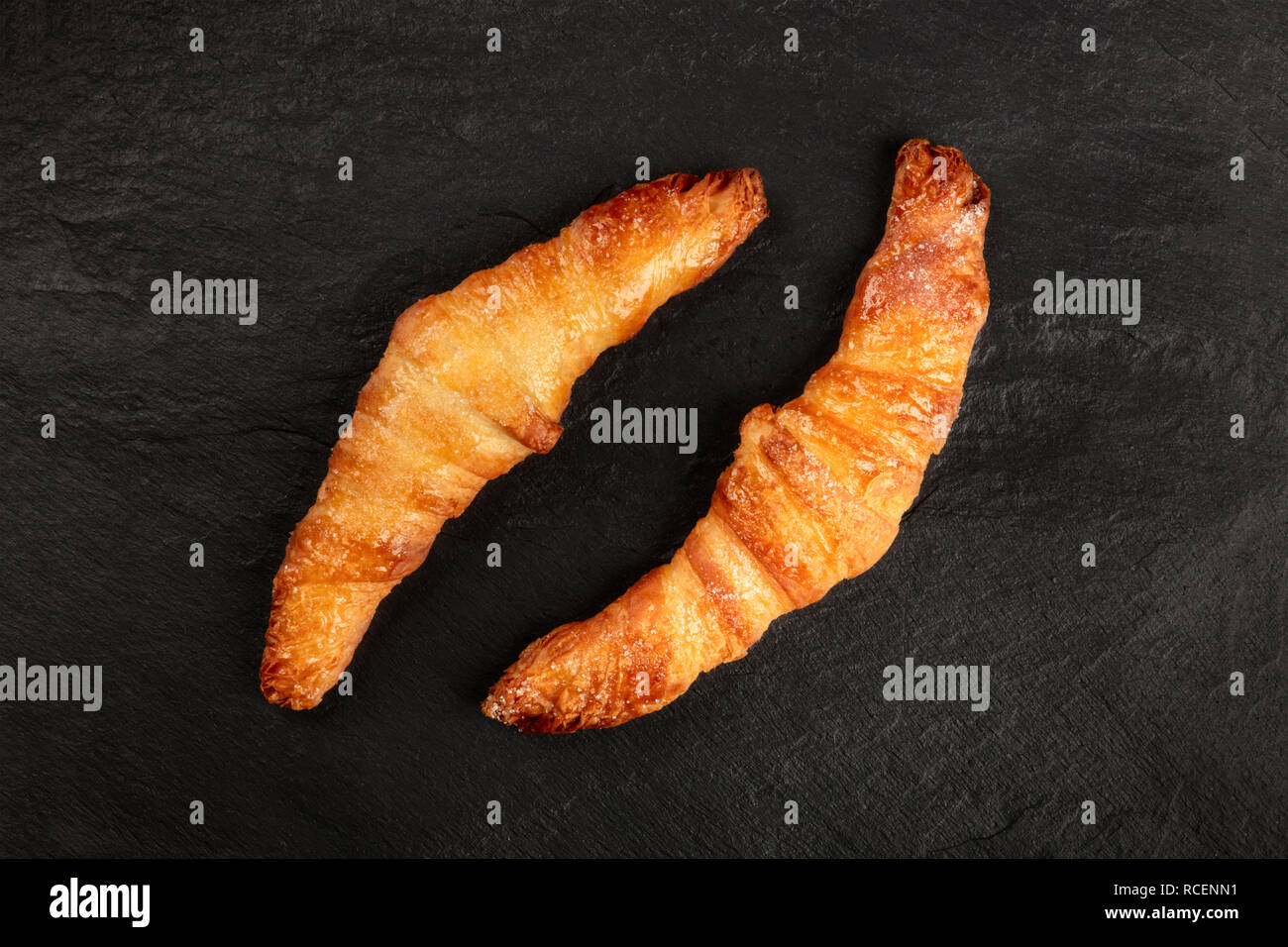 Two croissants on a black background, shot from above, with copy space - Stock Image