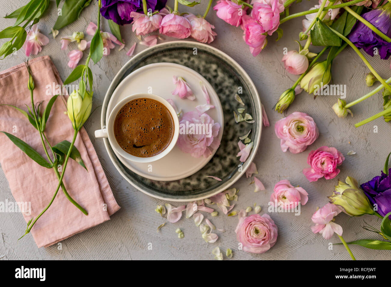 Upper view shot of a cup of coffee in the middle of floral frame of pink ranunculus and purple and yellow lisianthus - Stock Image