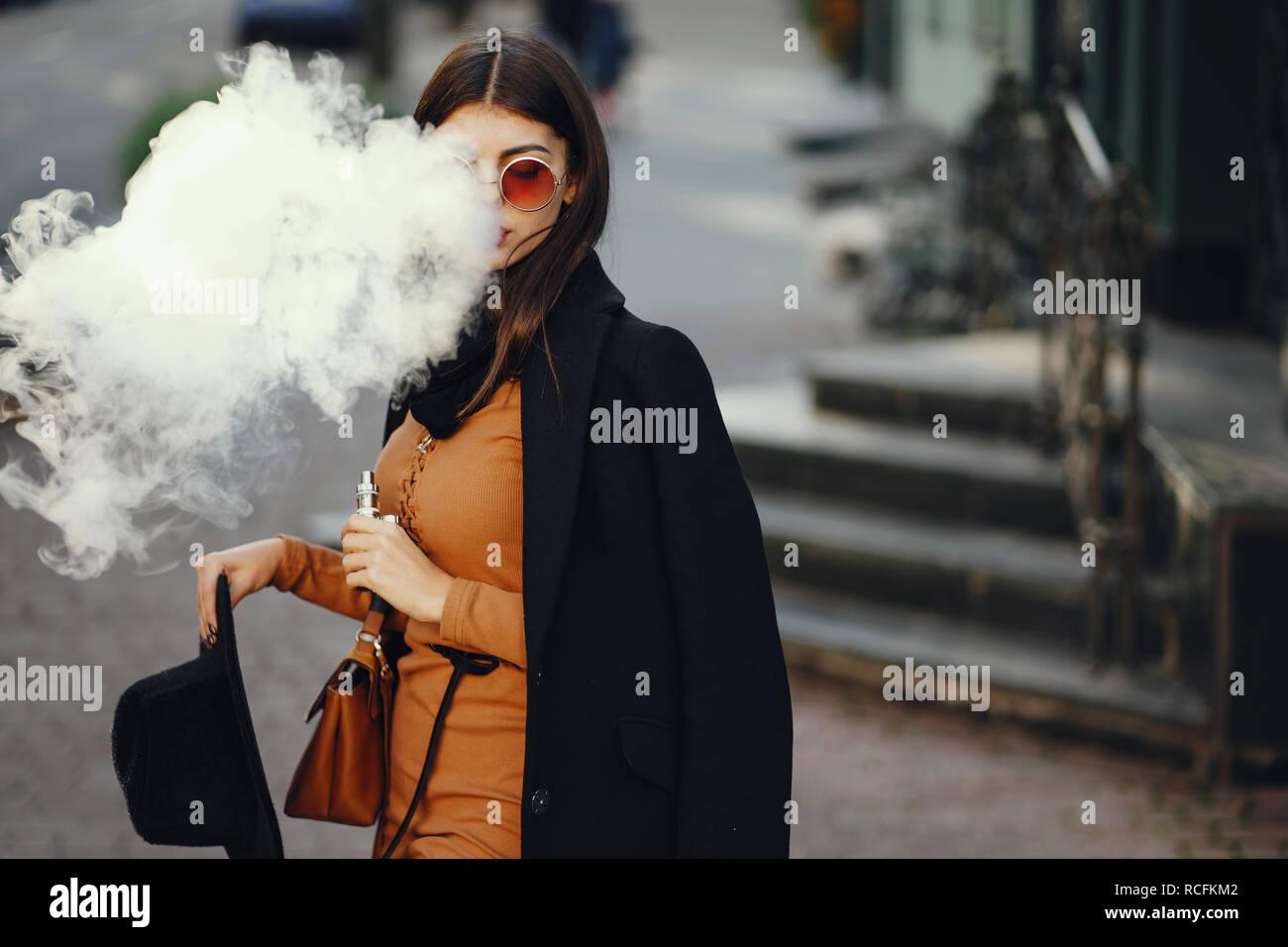 stylish girl smoking an e-cigarette - Stock Image