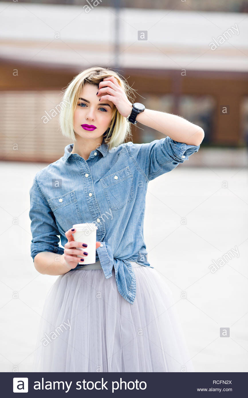 67d1bc3bc A portrait of a standing dreamy blonde girl with bright pink lips hoding a  cup of