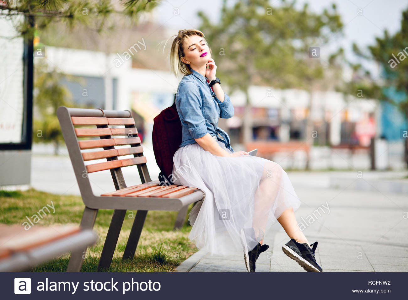 a9a5ef10 Young cute blond girl with short hair sitting on a wooden bench and  dreaming with eyes