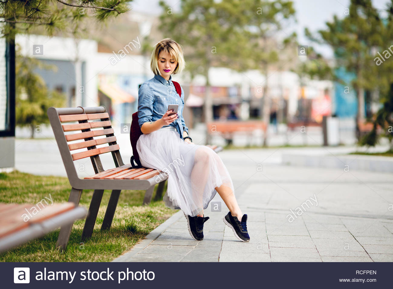 cd4af4d96 Young cute blond girl with short hair and bright pink lips sitting on a  wooden bench