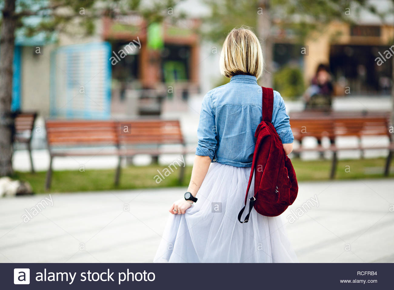 5ff52348df A portrait of the back of a girl holding marsala backpack wearing blue  denim shirt and grey tulle skirt. A girl walks in a city park with wooden  benches and ...