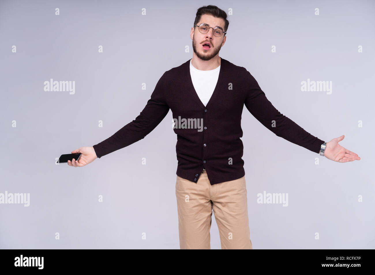 You will have problems man! Portrait of angry confused aggressive in bad mood guy shouting threatening in the loud-speaker of his smartphone, isolated on gray background. - Stock Image