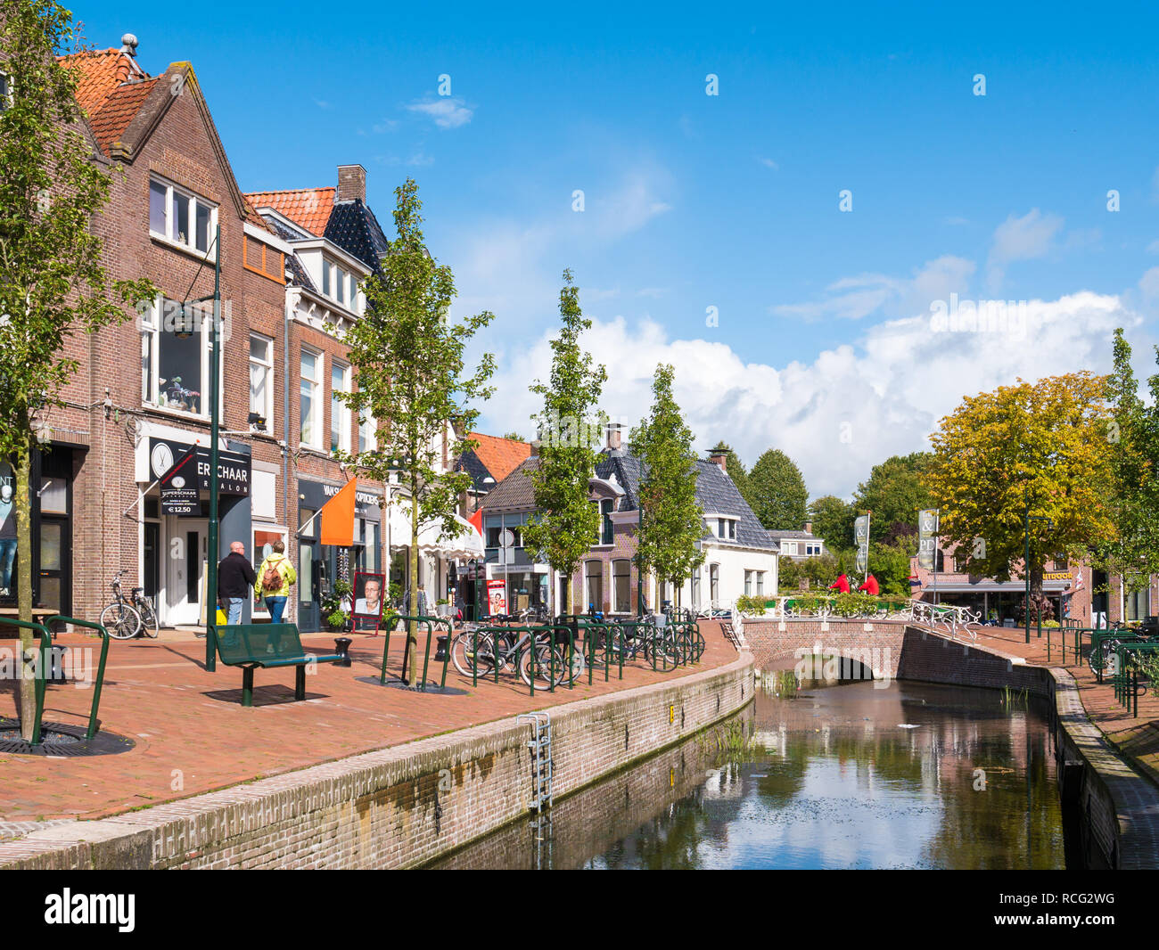 People walking on quayside with shops and canal in old town of Dokkum, Friesland, Netherlands Stock Photo