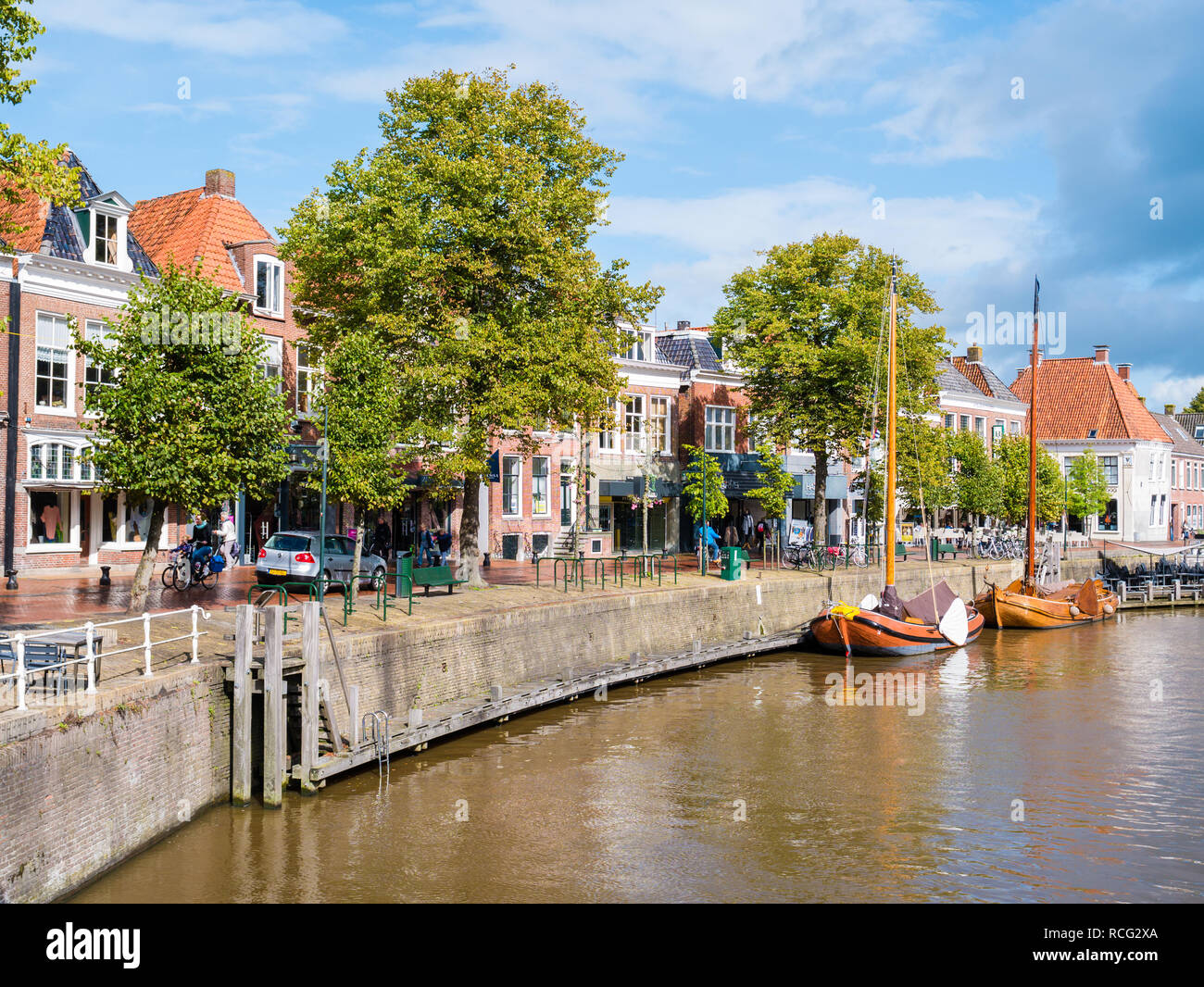 People and shops on quayside of historic harbour in old town of Dokkum, Friesland, Netherlands Stock Photo