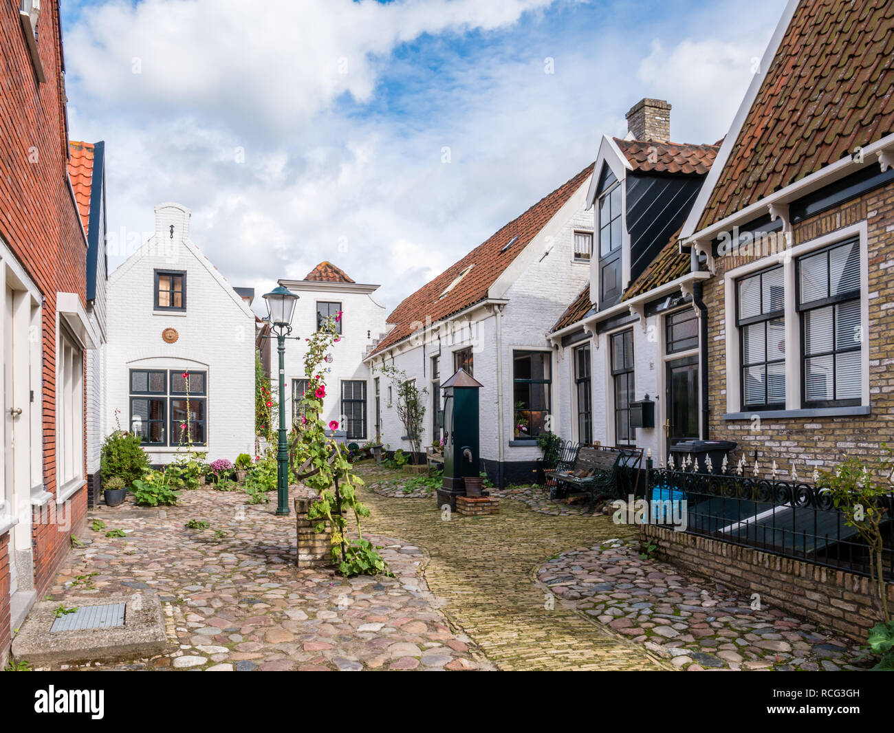 Historic courtyard Hofje with old white houses and water pump in Weverstraat of Den Burg town on Texel island, Netherlands Stock Photo