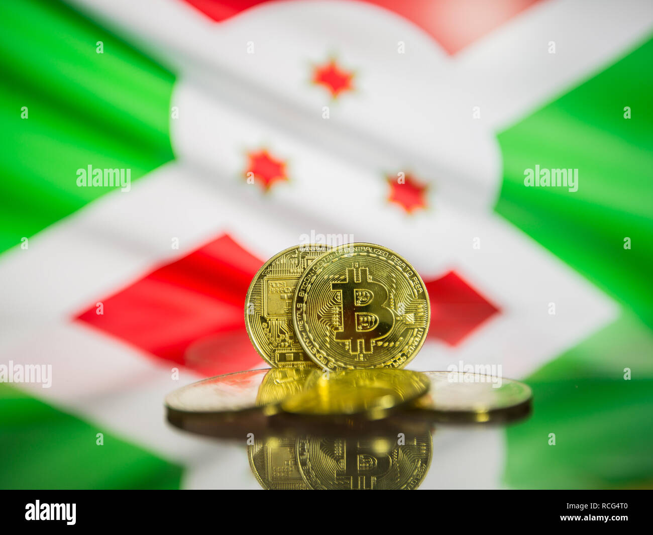 Bitcoin gold coin and defocused flag of Burundi background. Virtual cryptocurrency concept. - Stock Image