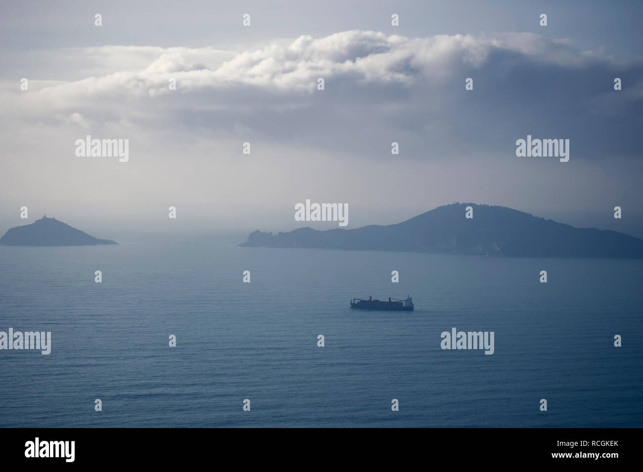 Misty evening with cargo ship, looking over the Gulf of Poets, La Spezia province, Italy. Palmaria Island visible. - Stock Image