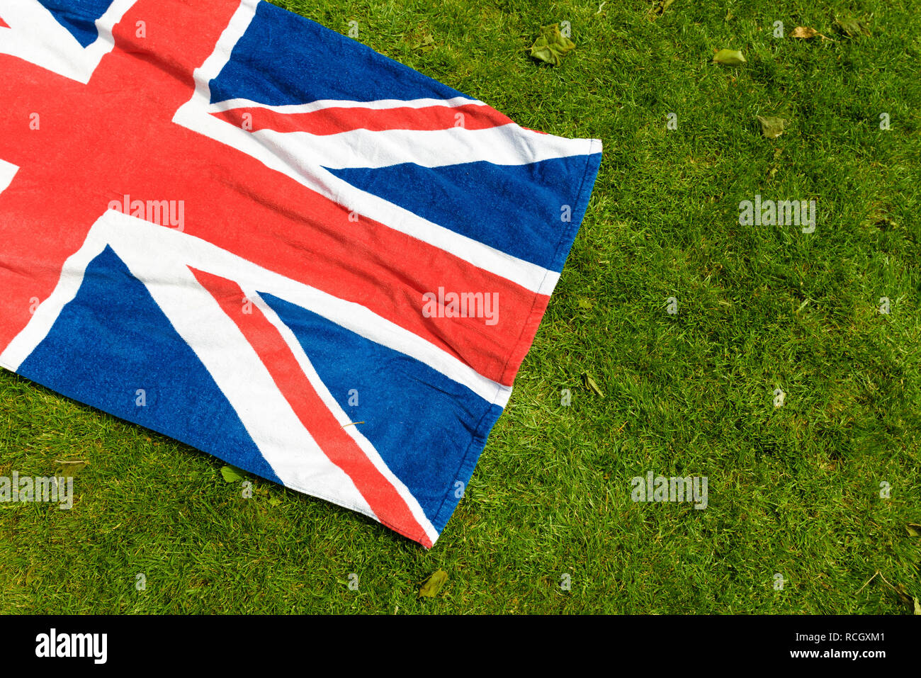 Union Jack on green grass. Great Britain and Northern Ireland flag in a park. Beach towel with the flag of the United Kingdom laid out for a picnic. - Stock Image
