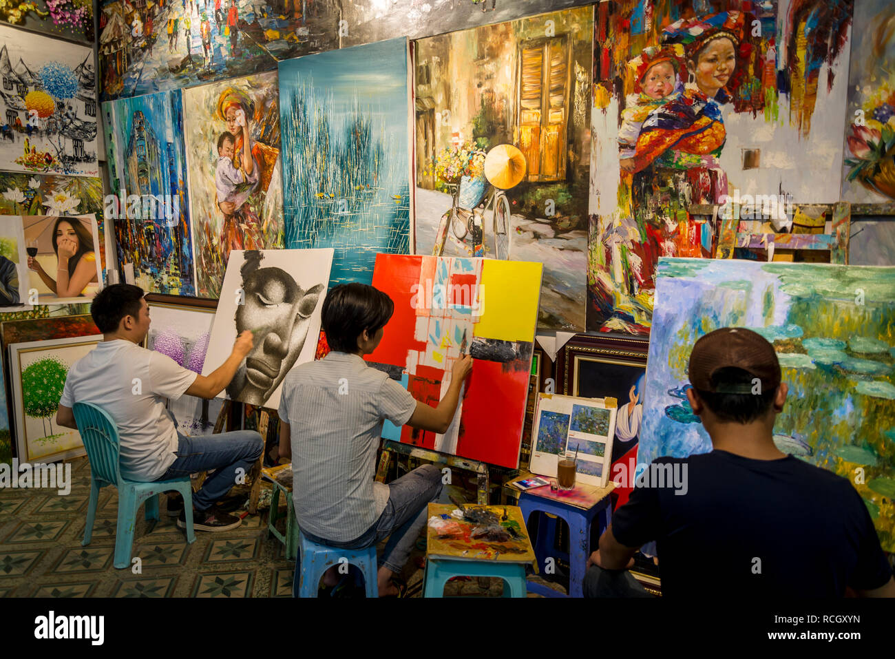 Artists in a commercial art gallery painting copies of well known European artworks, Hanoi, Vietnam - Stock Image