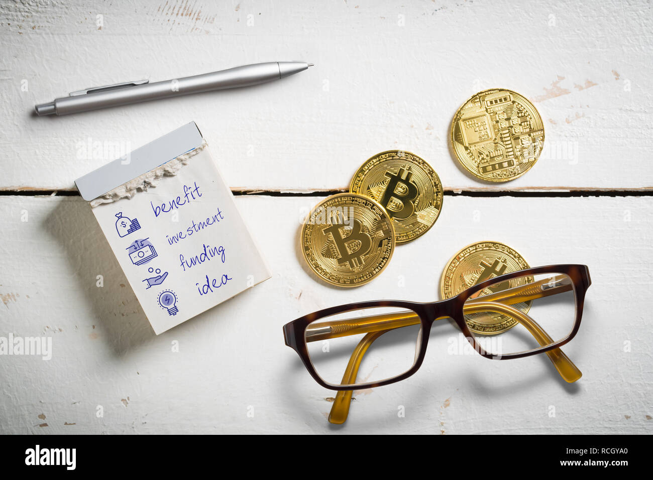 bitcoins with tear-off calendar with marketing symbols on wooden background - Stock Image